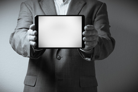 The image displays on individual dressed in a suit holding a tablet computer. Only the person photo