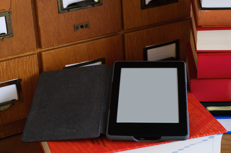 ebook: EBook Reader near stack of books in a library