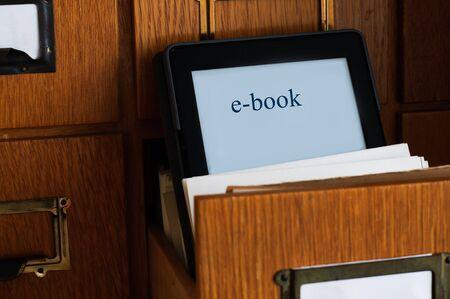 biblioteca: Lector de libros electrónicos en un catálogo de tarjeta de la biblioteca del cajón nuevo concepto de la tecnología