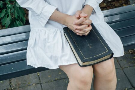 Woman hands praying with a bible in her knees outdoors 스톡 콘텐츠