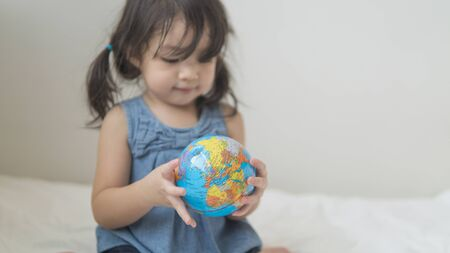 Close-up of globe ball in asian toddler hands.