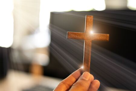 Hands holding wooden cross on, Church online concept. Worship at home concept. Stok Fotoğraf