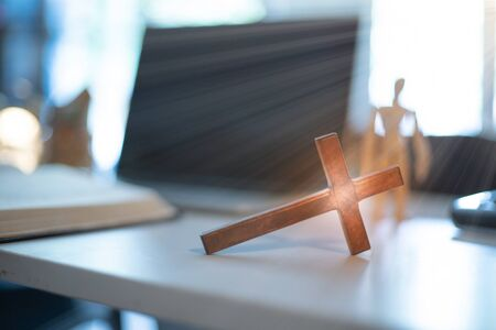 Cross over wood table with window light. online church concept.
