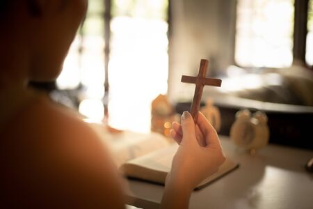 Asian woman praying and holding a cross with her bible on table. Online church from home concept. Stok Fotoğraf