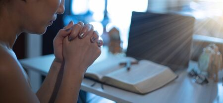 Hands praying by faith with laptop, book, notebook on it, praying position. Online church from home concept. Stok Fotoğraf