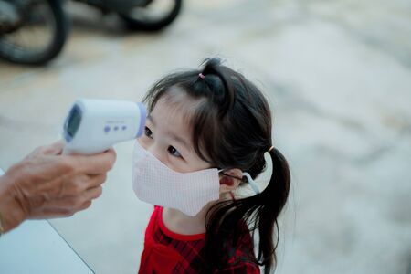 Asian girl measuring body temperature and wearing a face mask.