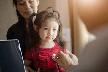 A girl looking a doctor when he examining by stethoscope and mother standing near her. Health concept. Stok Fotoğraf