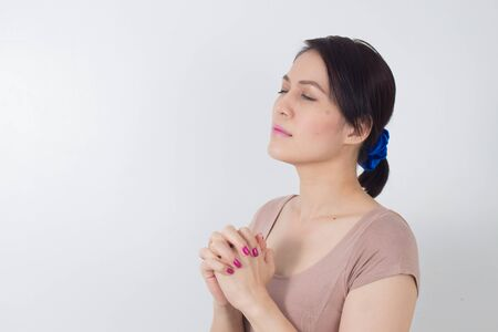 Asian woman hands praying to god with close her eyes.