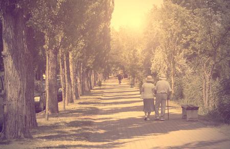 personas de espalda: Foto de la vendimia de la pareja de ancianos caminando en el parque un día soleado Foto de archivo