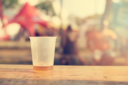 throwaway: Few beer in the plastic cup on wooden table, a sunny day
