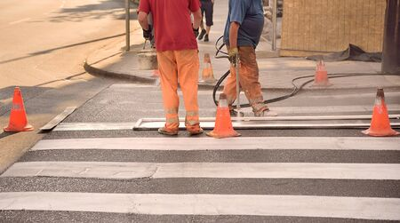 top down car: Workers making of a new pedestrian crossing on the road Stock Photo