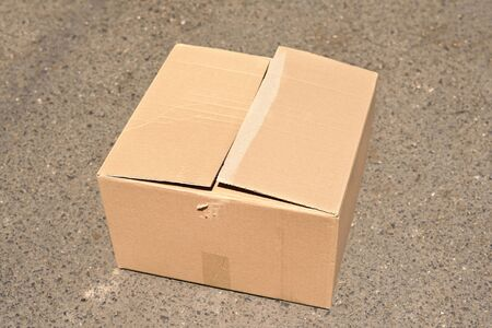 ship with gift: Corrugated cardboard box on asphalt