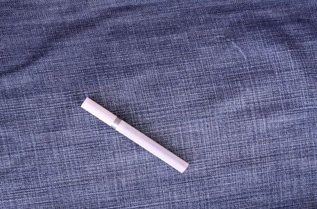 boodle: Closeup photo of cigarette on a blue jeans background