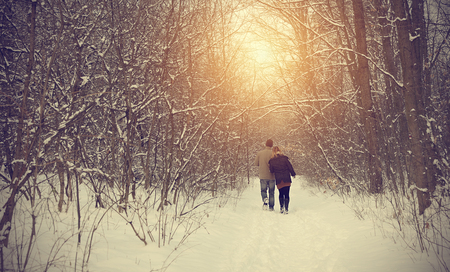 Couple on winter path in forest on a sunny day Banque d'images