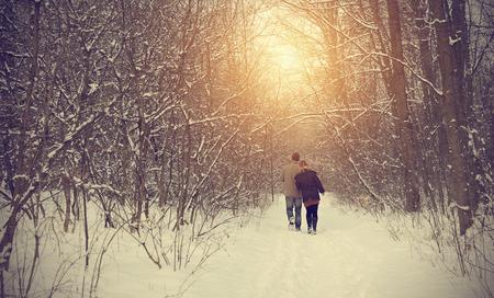 dia soleado: Pareja en el camino de invierno en el bosque en un día soleado
