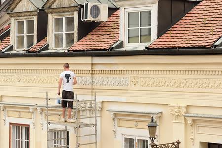 hombre pintando: Trabajador que pinta la pared, al aire libre Foto de archivo