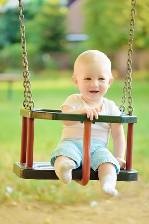 playground ride: Happy baby boy having fun on a swing ride at a playground a summer day Stock Photo