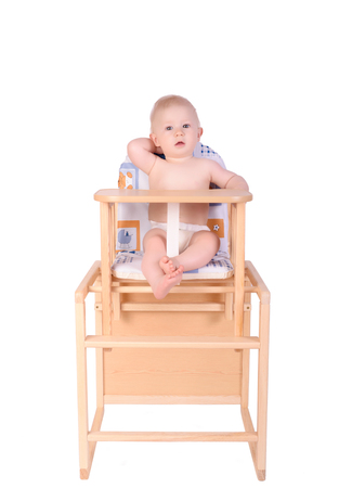 boyhood: Adorable baby in high chair isolated on white