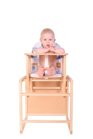 chłopięctwo: Adorable baby in high chair isolated on white