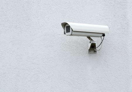 paranoia: CCTV security camera on a gray the wall