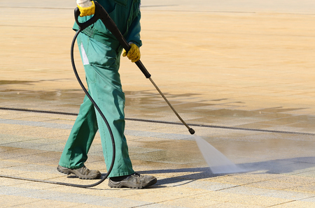 men at work: Wet cleaning of city streets with high-pressure cleaner