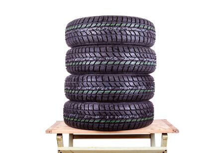 winter tires: Wet, winter tires isolated on wooden table, isolated