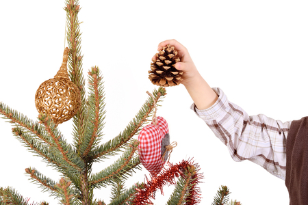 Child hand decorate the christmas tree on white background