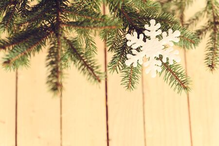 pine branch: Snowflake shape on pine branch a wooden background Stock Photo