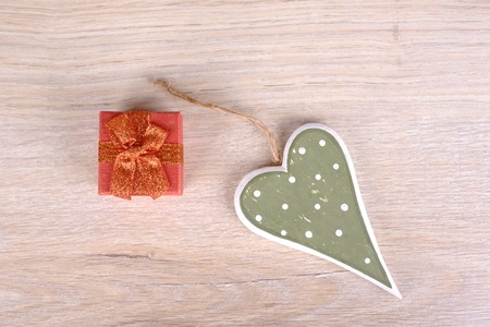 s shape: Retro heart with gift box on wooden background