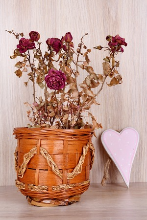 valentine s day: Dry red roses with heart on wooden background