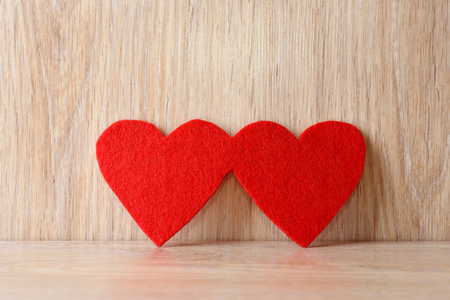s shape: Red hearts on wooden background. Love symbol