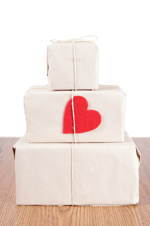 valentines day mother s: Red heart shape on package a wooden table