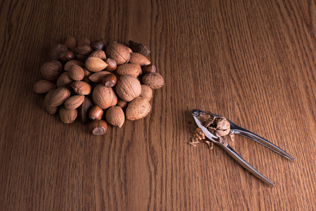 nut cracker: Different types of nuts on wooden background