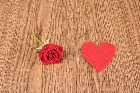 s shape: Red rose and heart shape on wooden background Stock Photo