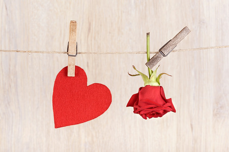 valentine s card: Red rose and heart shape hung on the rope Stock Photo