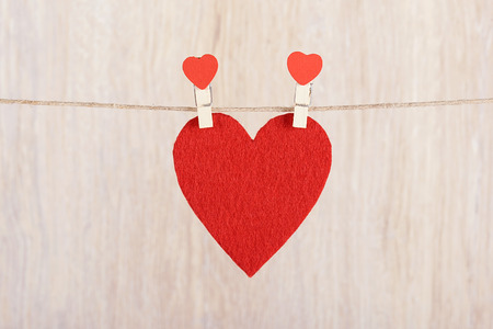 s shape: Red heart hung on the rope a wooden background