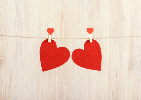 s shape: Two red hearts hung on the rope a wooden background Stock Photo