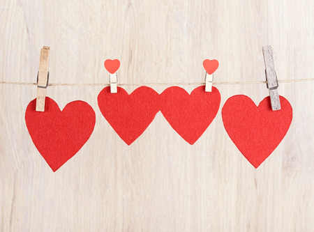 valentine s card: Four red hearts hung on the rope a wooden background