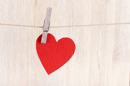valentine s card: Red heart hung on the rope a wooden background