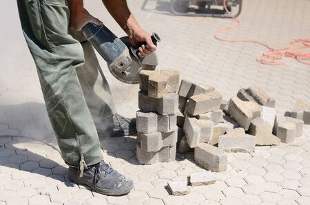 stone cutter: Builder worker with grinder machine, cutting flagstones in construction site Stock Photo