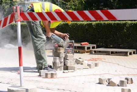 grinder machine: Builder worker with grinder machine, cutting flagstones in construction site Stock Photo