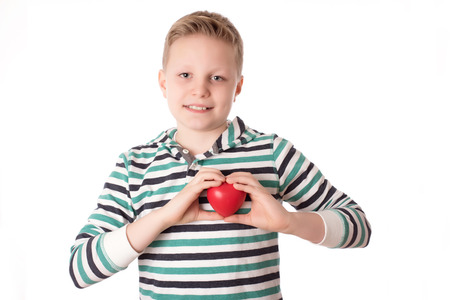blond boy: Young boy holding a heart over the white background Stock Photo