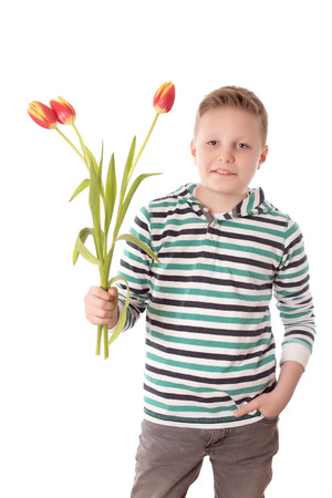 young boy smiling: Handsome young boy with tulips isolated on white background
