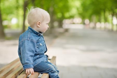 niños rubios: Niño sentado en el banquillo en el Parque Foto de archivo
