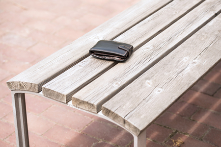 empty bench: Lost leather wallet on empty bench