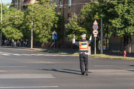 pulled over: Traffic policeman directing cars in a crossing road, detail