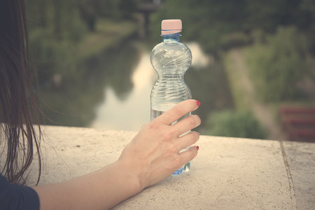 bottled water: Beautiful woman hand holding a bottled water, vintage view Stock Photo