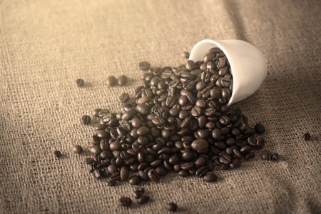 sackcloth: Cup pours coffee beans on sackcloth background