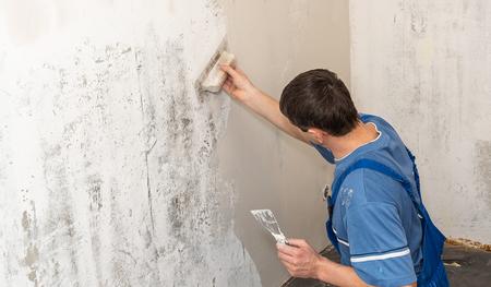 Handen stukadoor aan het werk. Toepassing van de pleister op de muur Stockfoto