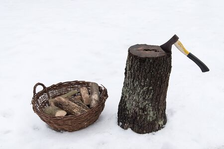 Ax in the stump a winters day in snow Stock Photo